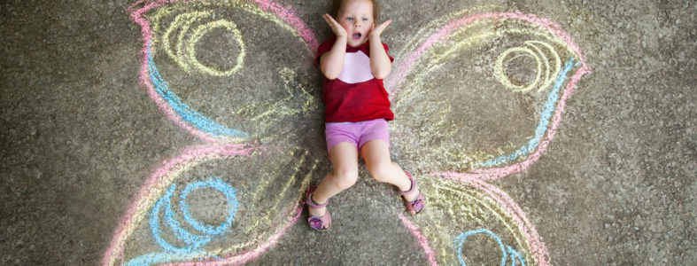 Little girl Butterfly, SURPRISE. Drawing with chalk on the pavement